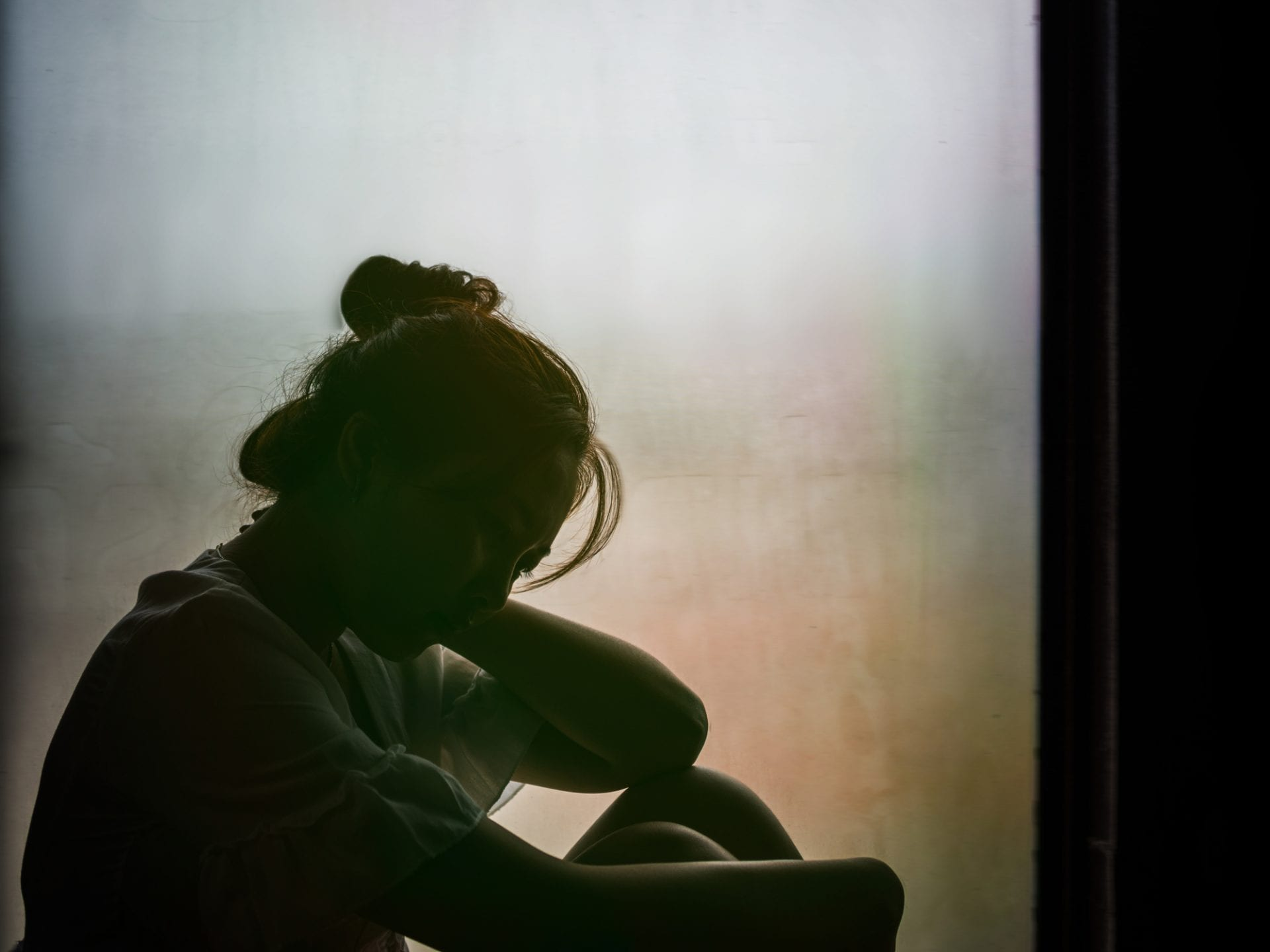 Vintage filtered on silhouette of depressed girl sitting on the window