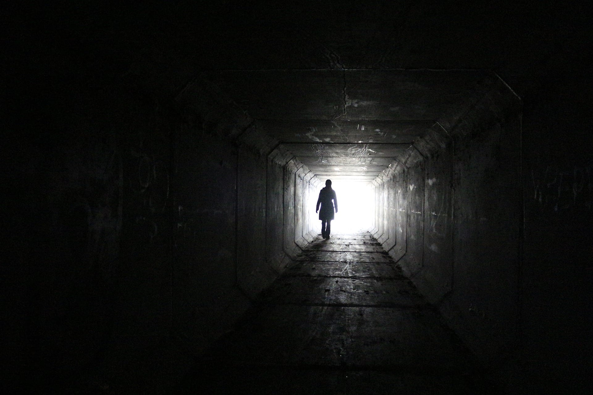 man looks down tunnel, mysterious