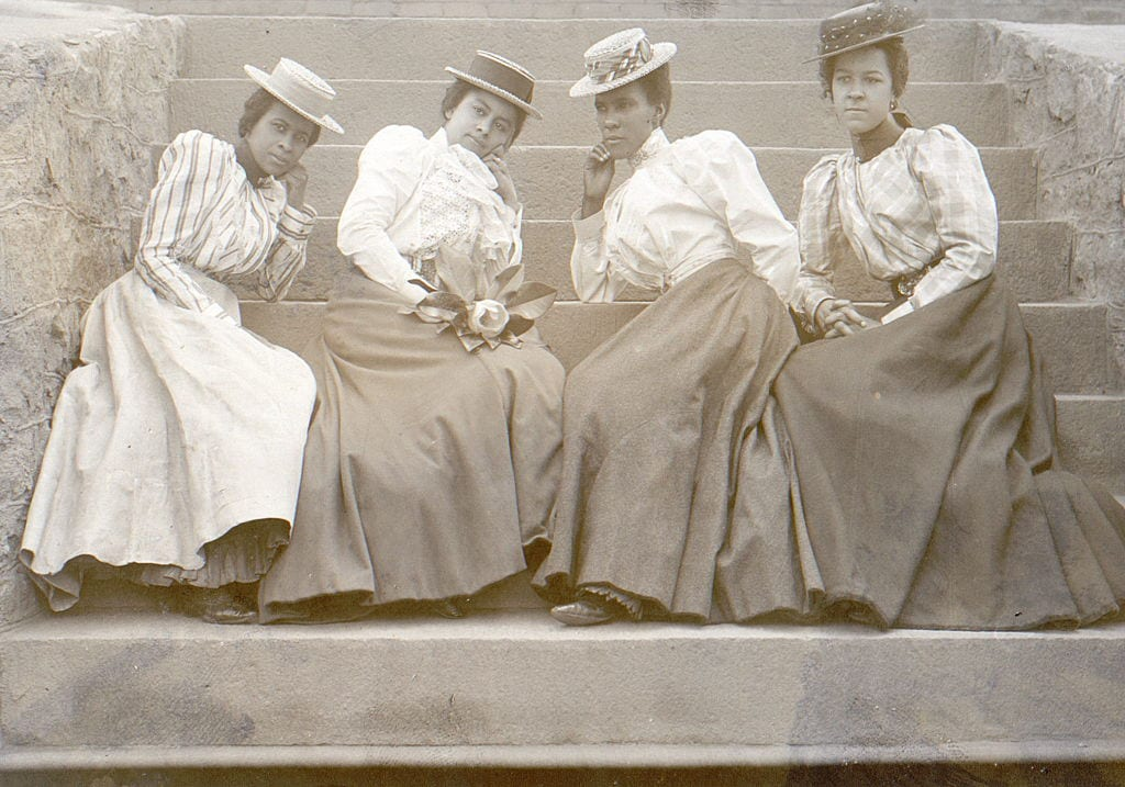Four African American women seated on the steps of a building at Atlanta University, Georgia. Photographer Thomas E Askew (1850-1914). Published 1899-1900.