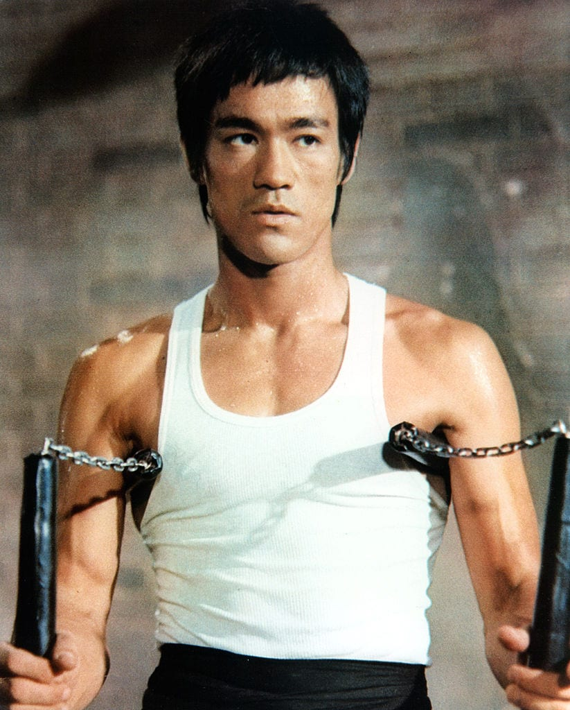Bruce Lee posing with nunchucks