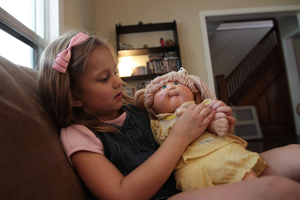 Megan plays with her mom's vintage Cabbage Patch doll at the family home