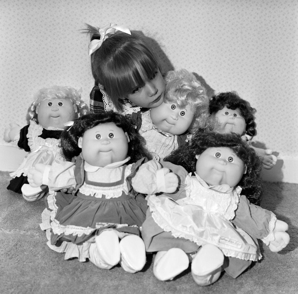 A young girl plays with her Cabbage Patch Dolls