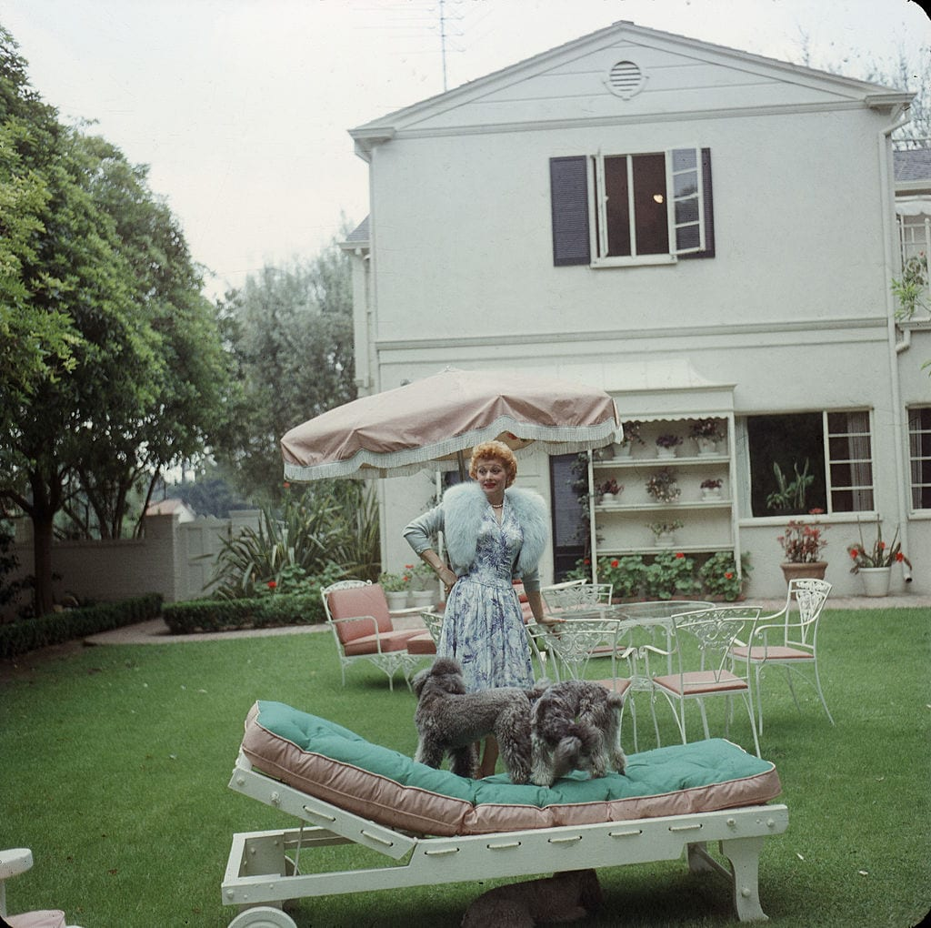 Lucille Ball and her dogs in her backyard