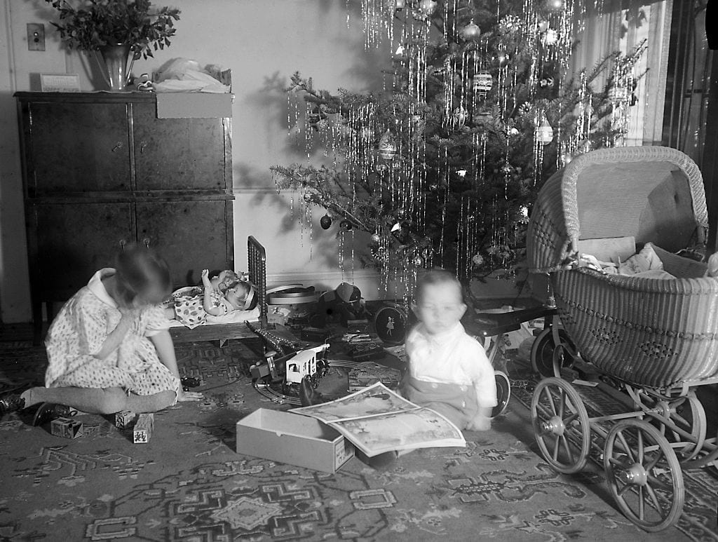 Boy and girl investigate their Christmas haul, ca. 1915.