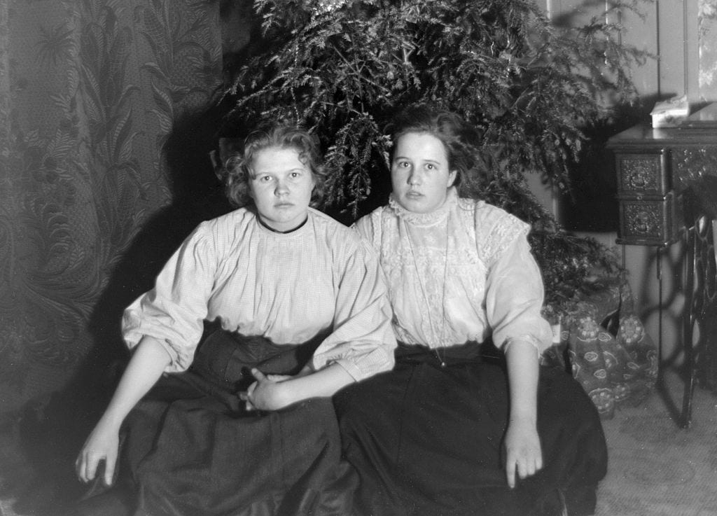 Sisters hold hands beside Christmas tree, ca. 1908