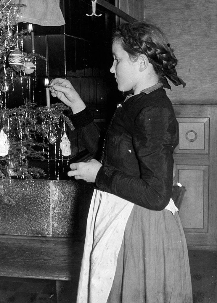 little girl hanging tinsel in a tree