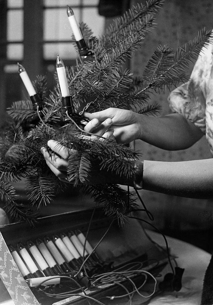Hands of a woman are putting a chain of lights on a Christmas tree - Photographer: Max Ehlert- Published by: 'Hier Berlin' 51/1937Vintage property of ullstein bild
