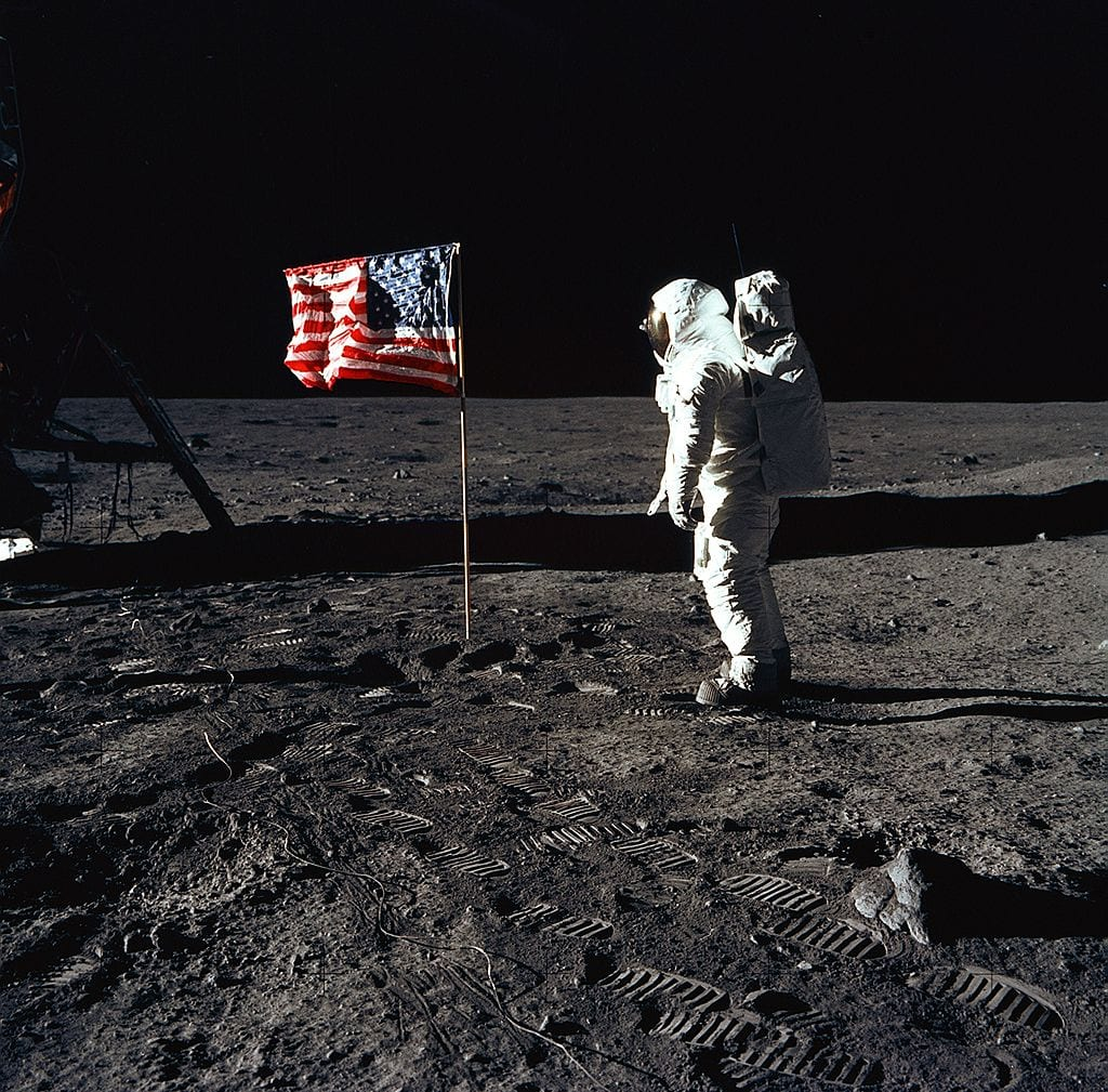 Astronaut standing next to american flag on the moon, astronaut on the moon, vintage colored photos