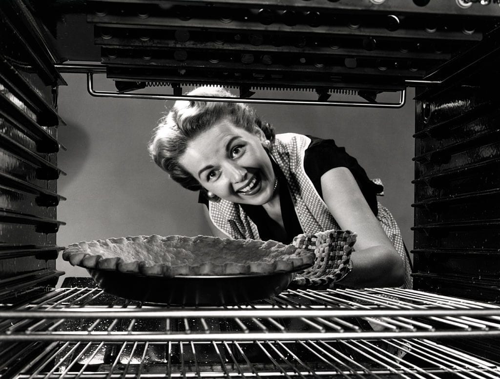 A woman reaches into the stove, trying to be a 'good housewife.'
