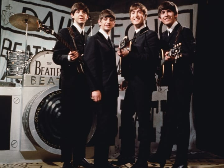 25th November 1963: Liverpudlian beat combo The Beatles, from left to right Paul McCartney, Ringo Starr, John Lennon (1940 - 1980), and George Harrison (1943 - 2001), performing in front of a camera-shaped drum kit on Granada TV's Late Scene Extra television show filmed in Manchester, England on November 25, 1963.