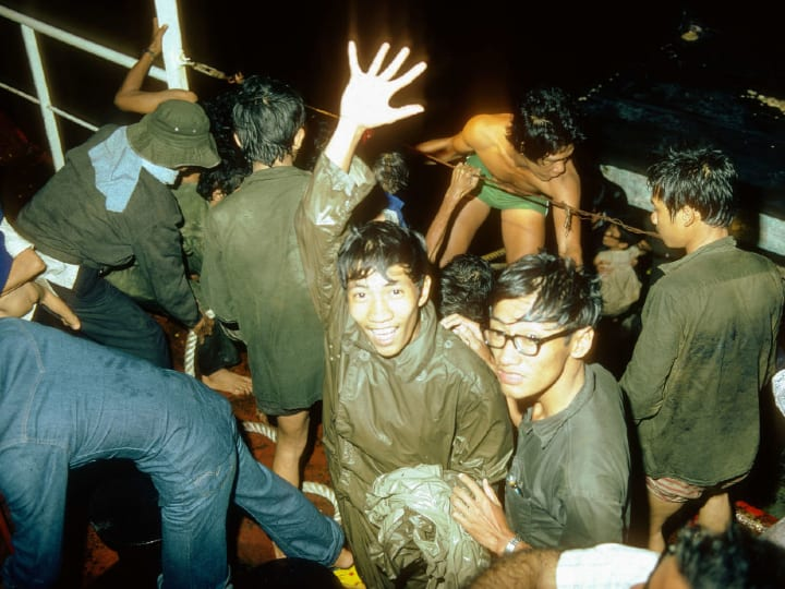 Soaking wet from the sea but happy to have survived the journey. Vietnamese Boat people get rescued from their nautical vessel in the middle of the night.