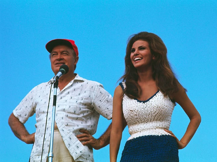 Comedian Bob Hope and actress Raquel Welch enertain troops at an unidentified outdoor site in Vietnam.