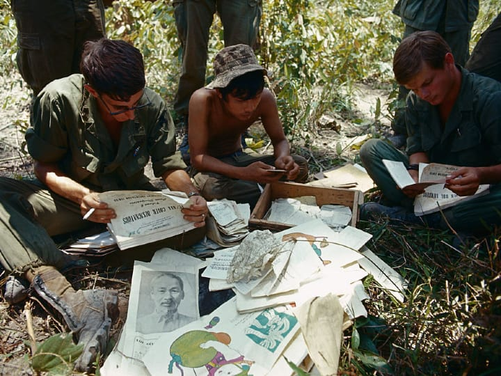 US Intelligence personnel examine captured documents found May 3 when US 11th Armored Cavalry Regiment soldiers raided Viet Cong bunker complexes some 3 miles from the Vietnam border.