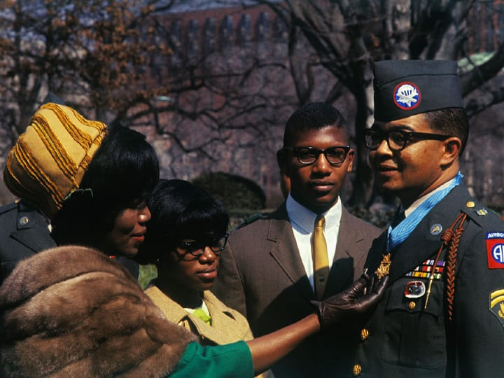 Mrs. Lawrence Joel of Winston-Salem, admires the Medal of Honor which President Johnson presented to her husband Army Specialist 6 Lawrence Joel, in a ceremony outside the White House.