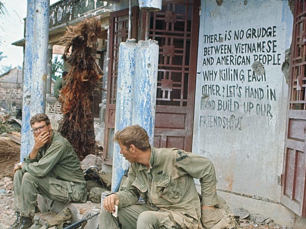 Members of the 1st Cav. rest in front of a Viet Cong propaganda lettering on a destroyed building. This village had been a Viet Cong supply base.
