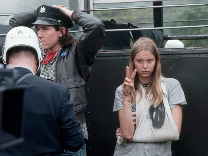 "A protester against the war in Vietnam gives the peace sign after being arrested during the ""May Day"" demonstrations in Washington, D.C. in 1971."