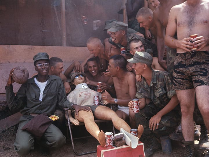 Marines scheduled to depart Vietnam have a few laughs with a life size female doll dressed in Marine shirt and shorts.