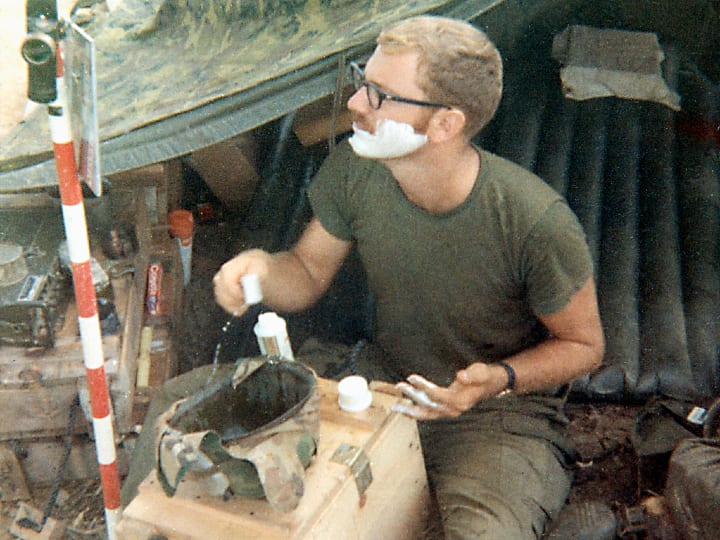 23 year old soldier shaves in front of his tent in Vietnam using his helmet as a water basin.