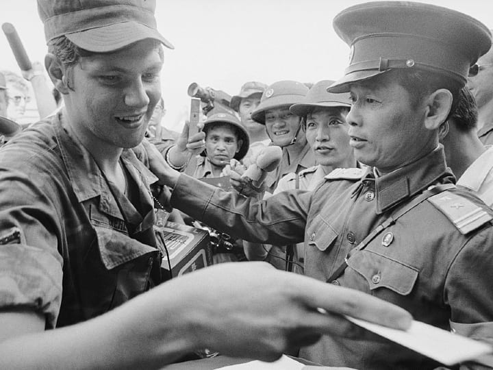 North Vietnamese Lieutenant Colonel Bui Tin (R), official spokesman for the North Vietnamese delegation to the JMC, shakes hands with an unidentified American Air Force sergeant at the departure of the last American servicemen from Vietnam, as the US role in Vietnam officially ended.