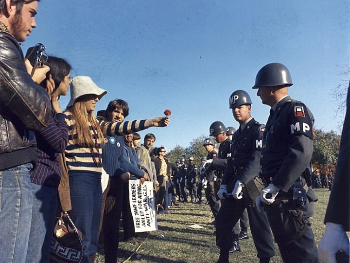 woman offers flower to military police during protest