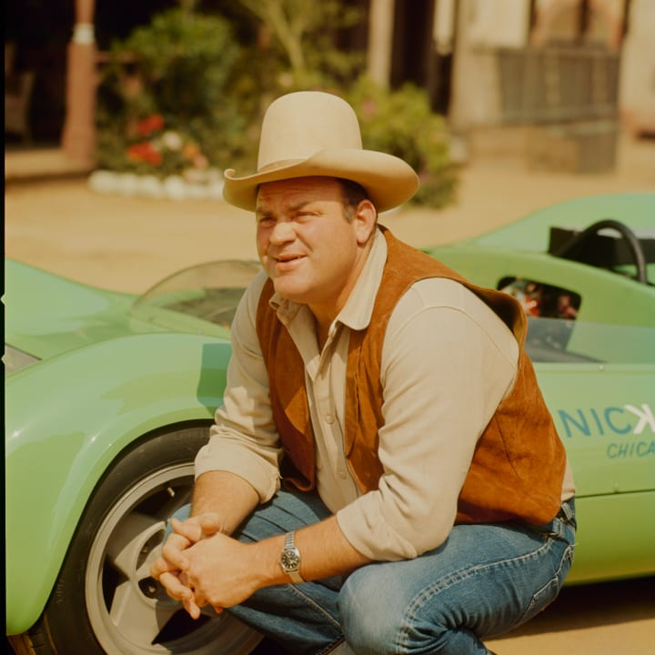Dan Blocker and Huffaker-built Nickey Chevrolet Genie Mk10, named the Vinegaroon. Posing on the The Western Street set at Paramount Studios in Los Angeles. Team owner/actor Dan Blocker, in costume, plays the character Hoss Cartwright on the TV drama Bonanza. Here he converses with Vinegaroon driver John Cannon.