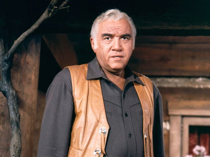 Lorne Greene (1915-1987), Canadian actor, wearing a tan leather waistcoat, dark grey shirt and dark grey trousers in a publicity portrait issued for the US television series, 'Bonanza', USA, circa 1970. The western drama starred Greene as 'Ben Cartwright'