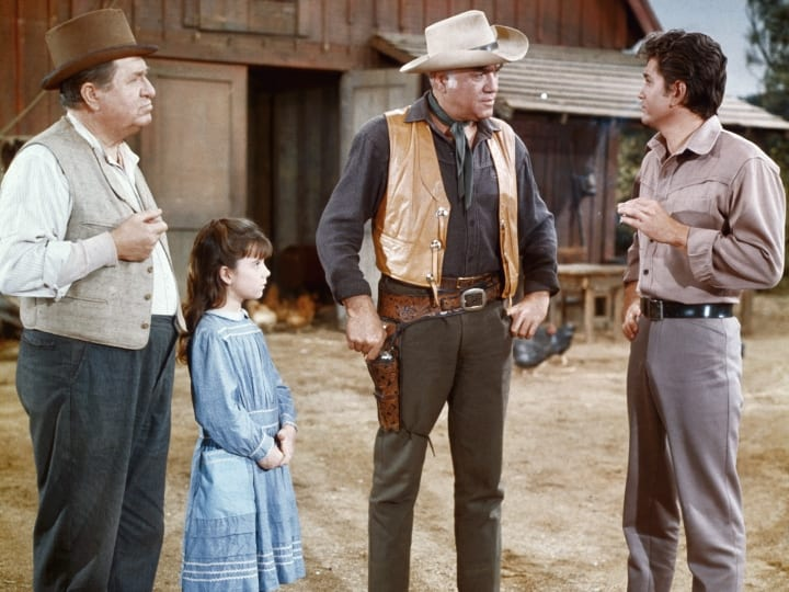 "Hollywood: Actor Stu Erwin in a scene from the television series, ""Bonanza"" in which he guest starred. With him are Lorne Greene as Pa Cartwright and Mike Landon as his son, ""Little Joe."" The young actress is not identified."