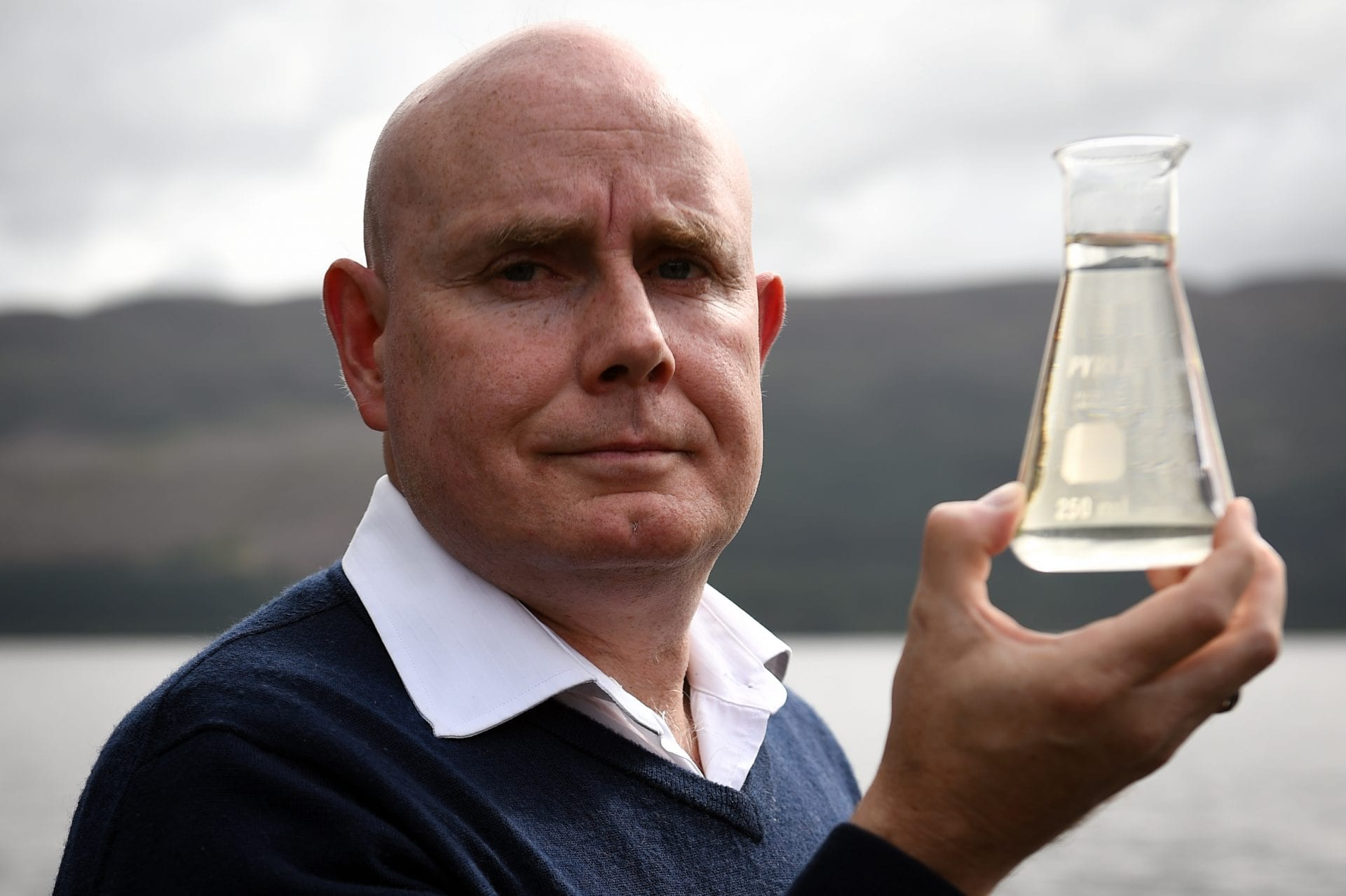 Professor Gemmell holding a beaker of water