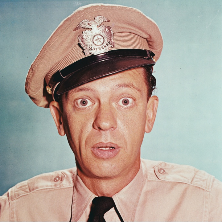 Don Knotts (1924-2006), US actor, in costume in a studio portrait, against a blue background, issued as publicity for the television series. 'The Andy Griffith Show', USA, circa 1965. The television comedy starred Knotts as 'Deputy Barney Fife'.