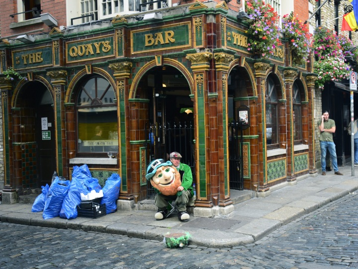 A man dressed in a leprechaun costume hired to attract customers to a Dublin, Ireland, pub takes a break in front of the pub in Dublin's Temple Bar district