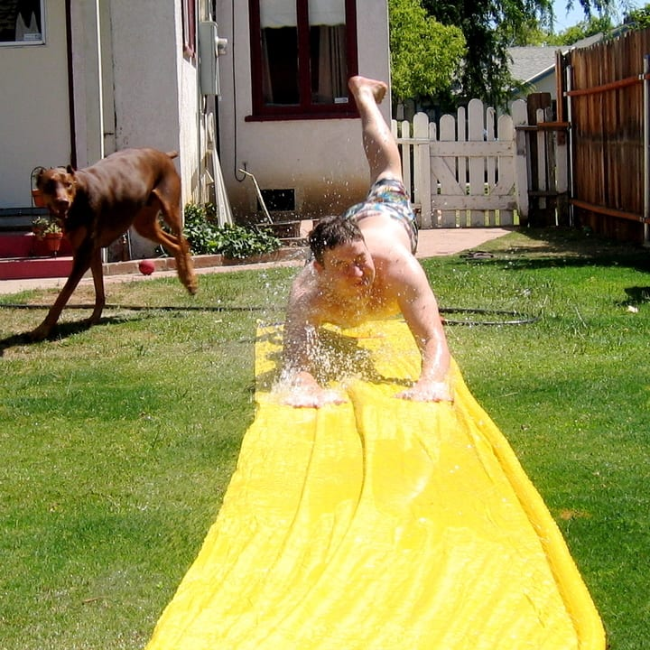 kid playing with slip and slide
