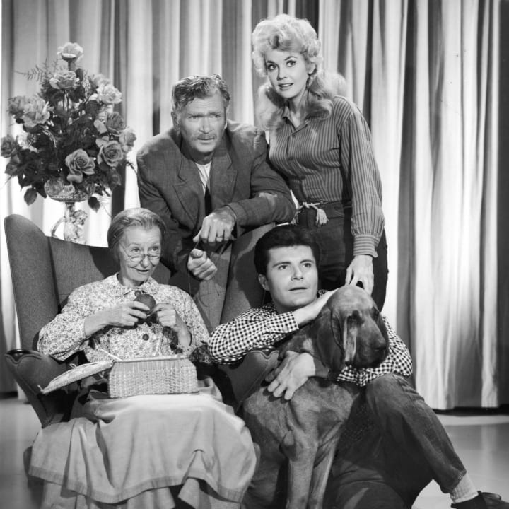 Promotional portrait of the cast of the television series, 'The Beverly Hillbillies.' Clockwise (from left) Irene Ryan (1902 - 1973), Buddy Ebsen (1908 - 2003), Donna Douglas and Max Baer Jr, holding the family dog, Duke, 1966.