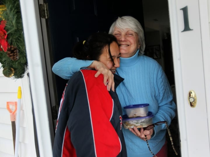 Treehouse resident Liz Poudrier hugs Sarah DAmato,19, who had just delivered her a hot Thanksgiving meal. DAmato wanted to give back to the community that raised her and has for the past few years prepared a Thanksgiving meal, which she distributes to all the elders at Treehouse. DAmato was placed in 25 foster families by the time she was 8 years old and was then adopted by Mary and Jack DAmato . The family spent the last 10 years living in the Treehouse community, where Sarah has flourished. She is a recent high school graduate and has just begun taking courses at Holyoke Community College I have like six grandmas here, says DAmato