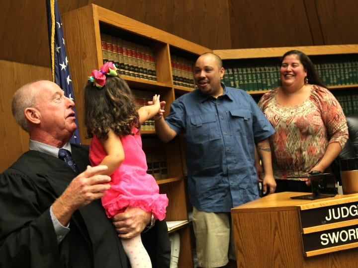 Judge Daniel Swords of Hampden Juvenile Court in Springfield holds Alexandra Rubio after adoption proceedings in his courtroom. The family had waited almost two years for the adoption to go through. Angel and Sandra Rubio laugh as Alexandra gives her dad a high-five in the courtroom. Its great to have a day like this; I wish we had more, says Swords.
