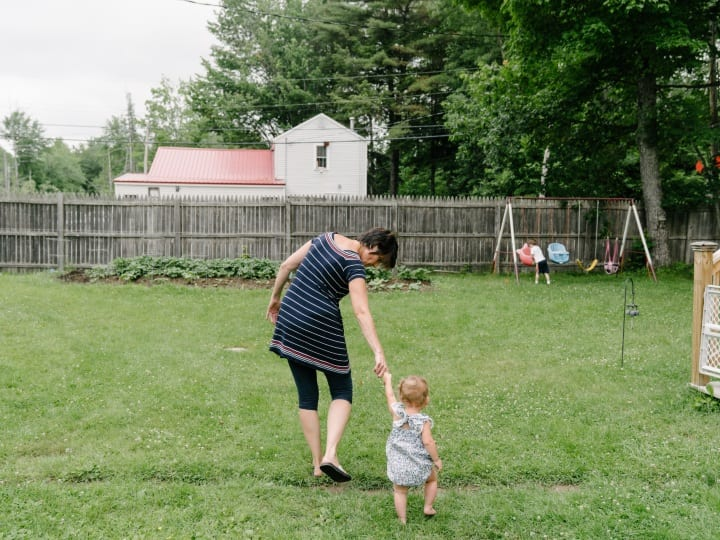 Debbie McLaughlin, of Greenbush, Me., guides an infant in foster care into her backyard to play with her 3-year-old grandson on Friday, June 30, 2017. McLaughlin and her husband are fostering their grandson, who was born drug-affected to their daughter, along with an infant from another family. With more than 1,000 children born drug-affected in Maine each year, the foster care system in Maine is stretched thin to accommodate the growing crisis of children in need of healthy, safe, drug-free homes. In the past four years, McLaughlin estimates she and her husband have fostered around 15 children.