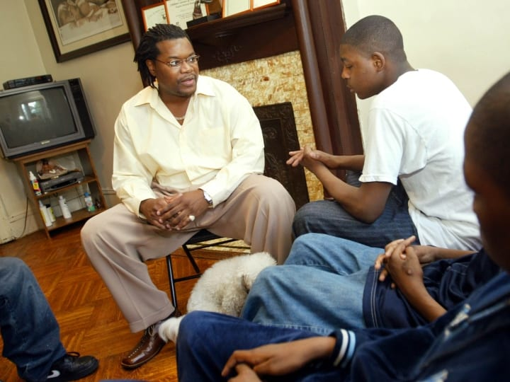 Stephen McCall talks with his four foster children June 10, 2003 in the Crown Heights neighborhood of Brooklyn in New York City. McCall, 35, has been a foster parent for five years, taking the four teenagers under his wing. More than 25,000 children are in foster care to 17,000 parents in New York City, and New York's Administration for Children's Services has launched new campaigns to encourage more potential foster parents to take adolescent and special needs children.