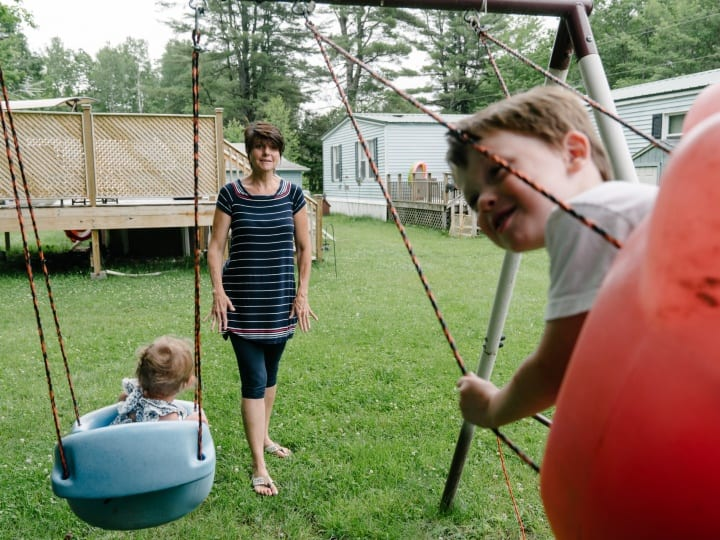 Debbie McLaughlin, of Greenbush, Me., swings an infant and her 3-year-old grandson, both in foster care, her backyard on Friday, June 30, 2017. McLaughlin and her husband are fostering their grandson, who was born drug-affected to their daughter, along with an infant from another family. With more than 1,000 children born drug-affected in Maine each year, the foster care system in Maine is stretched thin to accommodate the growing crisis of children in need of healthy, safe, drug-free homes. In the past four years, McLaughlin estimates she and her husband have fostered around 15 children.