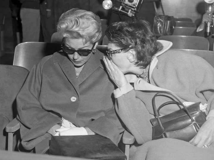 Friend whispering in Lana Turner's ear during trial