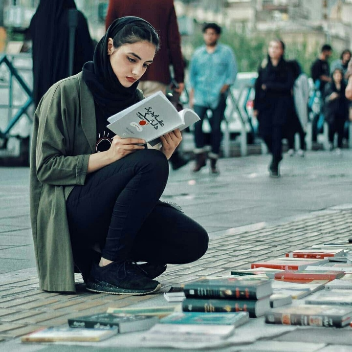 woman reading, streets of Tehran, books